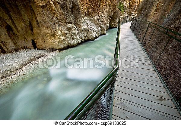 Wooden bridge on river - csp69133625