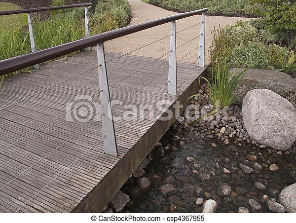 wooden bridge over pebbly pond - csp4367955