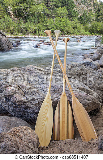wooden canoe paddles and mountain river - csp68511407