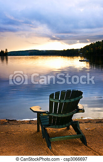 Wooden chair at sunset on beach - csp3066697