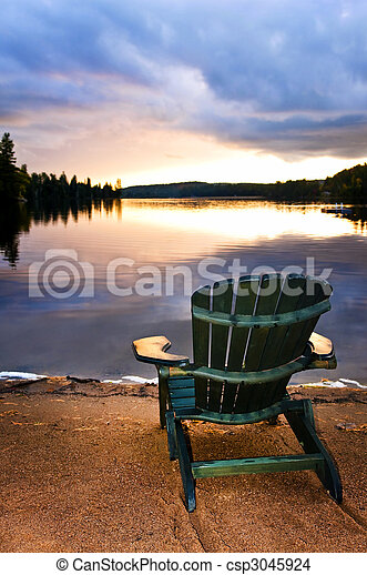 Wooden chair at sunset on beach - csp3045924