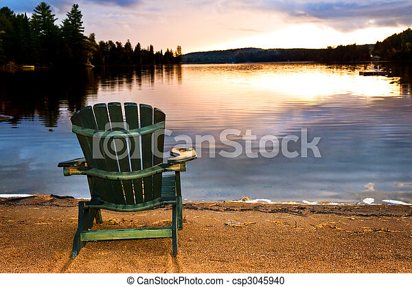 Wooden chair at sunset on beach - csp3045940
