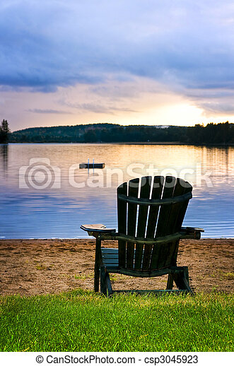 Wooden chair at sunset on beach - csp3045923