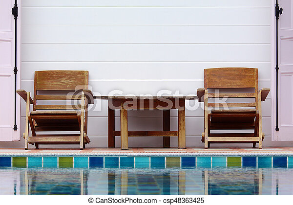 Wooden chair on ground beside swimming pool - csp48363425