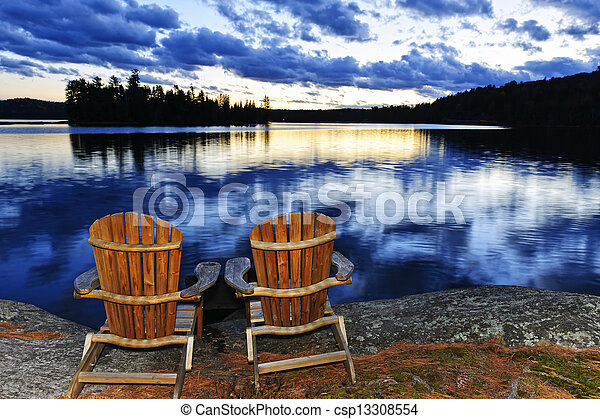 Wooden chairs at sunset on lake shore - csp13308554