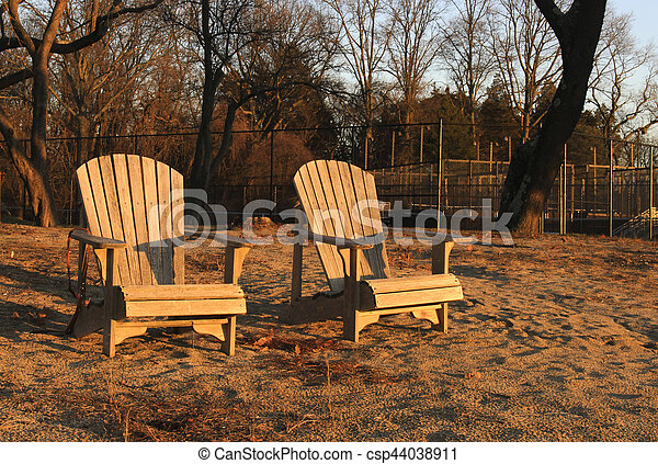 wooden chairs on beach at sunset - csp44038911