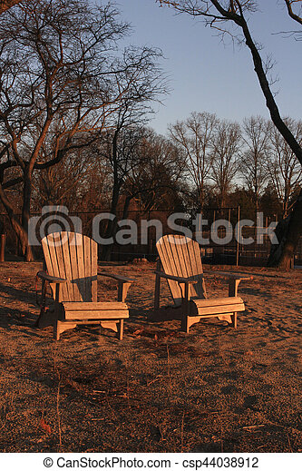 wooden chairs on beach at sunset - csp44038912