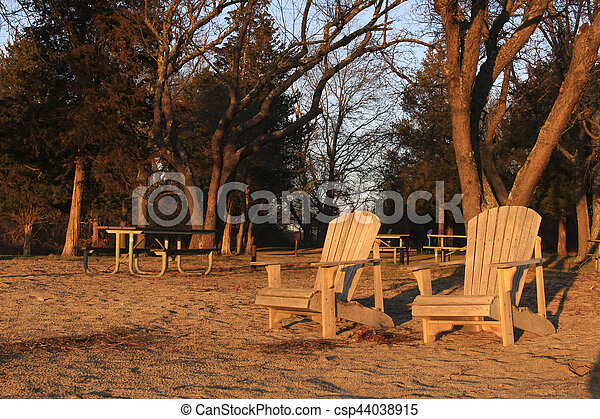 wooden chairs on beach at sunset - csp44038915