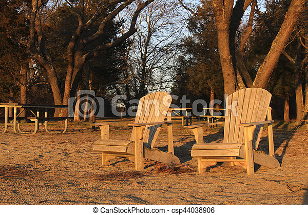 wooden chairs on beach at sunset - csp44038906