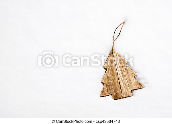 Wooden Christmas tree decoration on white snow - csp43584743