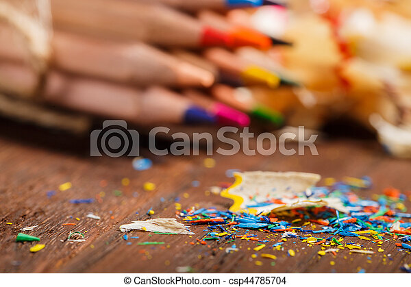 Wooden colorful pencils with sharpening shavings, on wooden table - csp44785704