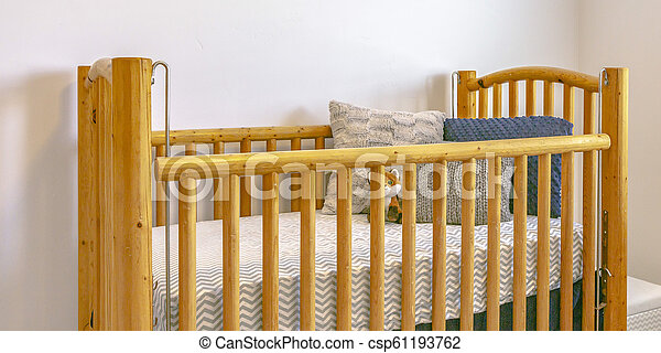 Wooden crib with mattress pillows and stuffed toy - csp61193762