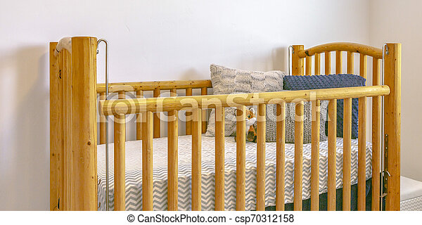 Wooden crib with mattress pillows and stuffed toy - csp70312158