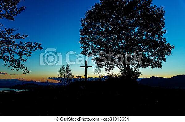 wooden crosses sit upon a hill in the sunset with tree and lake - csp31015654
