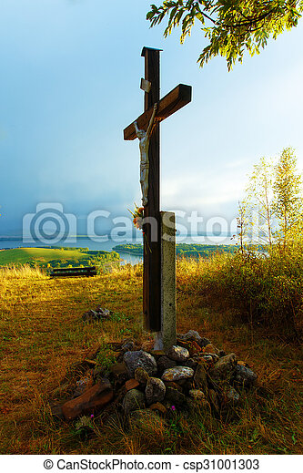 wooden crosses sit upon a hill in the sunset with tree and lake. - csp31001303