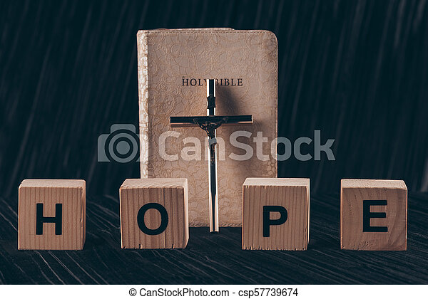 wooden cubes with word Hope and bible with cross on black table - csp57739674
