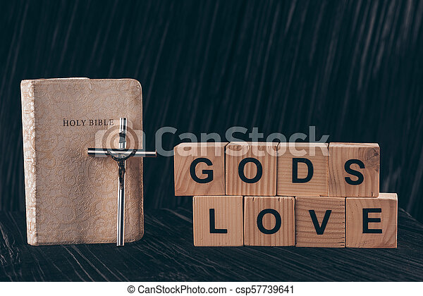 wooden cubes with words Gods Love and bible on black table - csp57739641