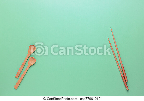 Wooden Cutlery: spoons and Chinese chopsticks on a green background. Zero waste, plastic free. - csp77061210