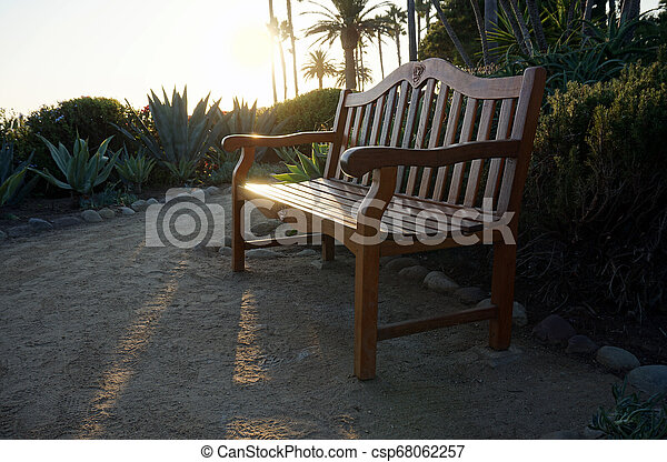 Wooden deck chairs on the beach at sunset. - csp68062257