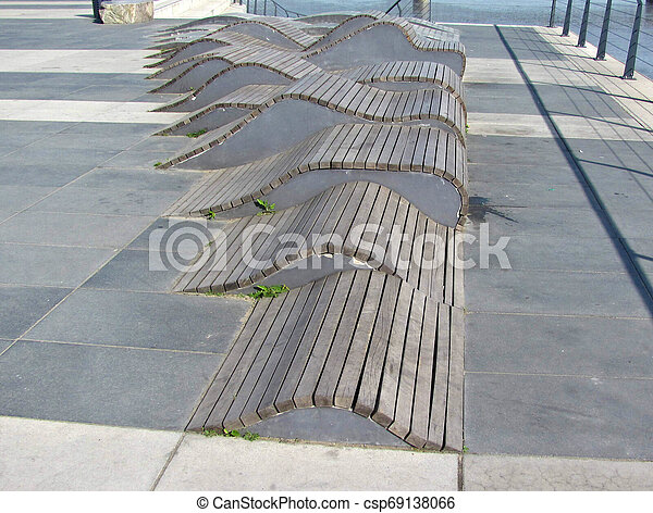 Wooden deck chairs, waves of wooden planks, couches, a place to rest. - csp69138066