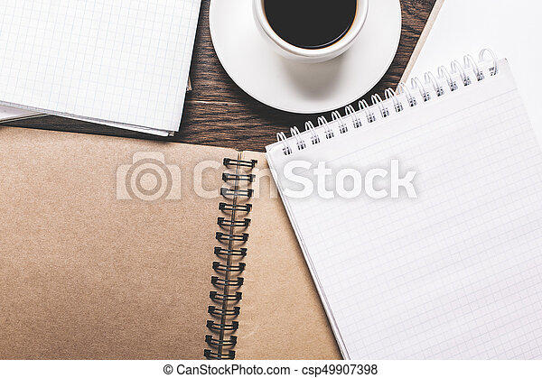 Wooden desktop with empty spiral organizer, coffee cup and other supplies. Mock up, Top view