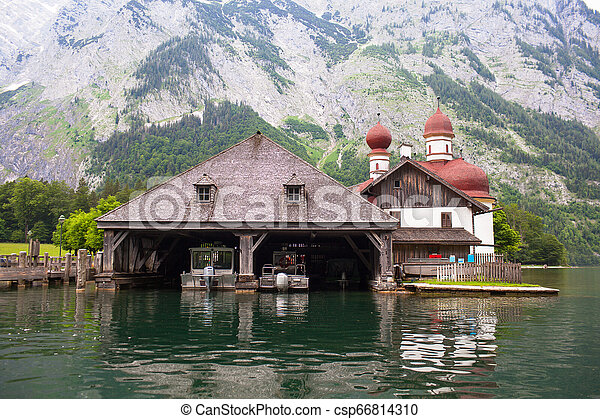 Wooden dock for boats with a temple and mountains in the background on Konigssee Lake, Austria - csp66814310