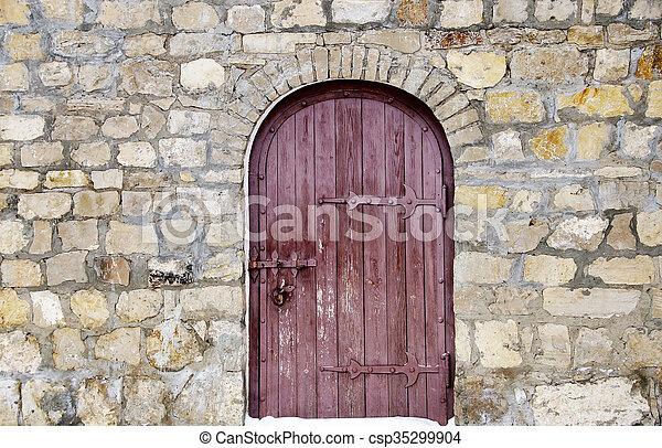 wooden door in a stone wall - csp35299904