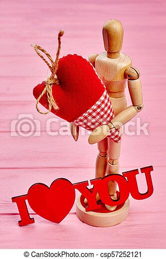 Wooden dummy mannequin in love holding heart. - csp57252121