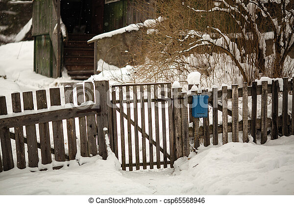 Wooden fence and gate near the house. Snowy winter on the street in the Russian village. - csp65568946