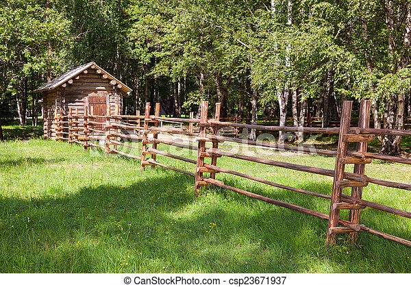 Wooden fence with small wooden house in countryside - csp23671937