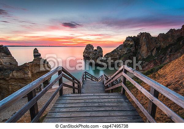 Wooden footbridge walkway to beautiful beach Praia do Camilo on coast of Algarve region, Portugal - csp47495738