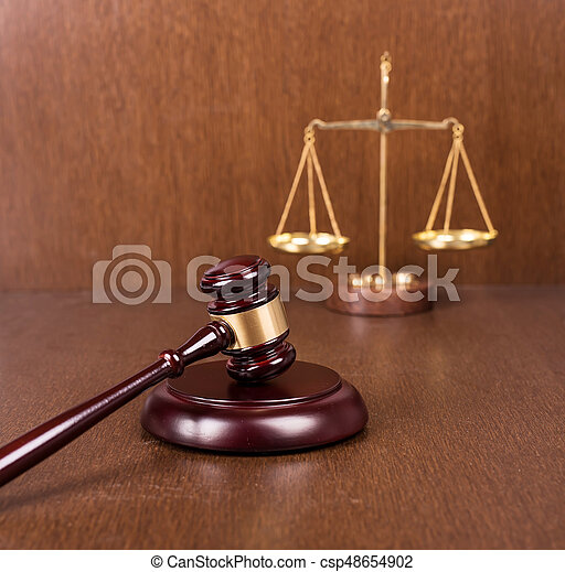 Wooden gavel with scales on wooden table, law concept - csp48654902