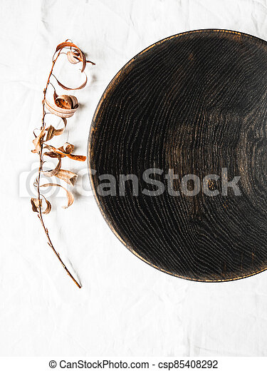Wooden homemade big black bowl and dry branch with leaves on white cloth background. Top view. Copy space - csp85408292