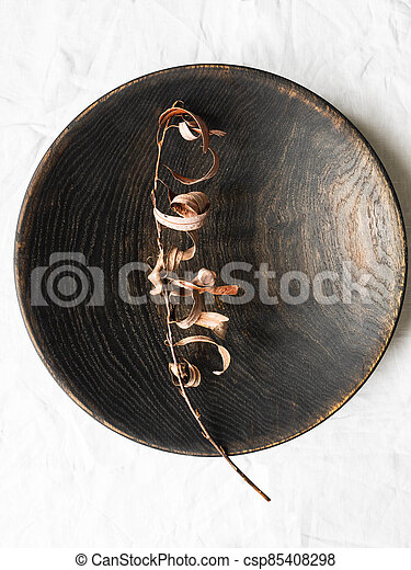 Wooden homemade big black bowl and dry branch with leaves on white cloth background. Top view. Copy space - csp85408298