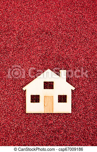Wooden house shape on red glitter background - csp67009186