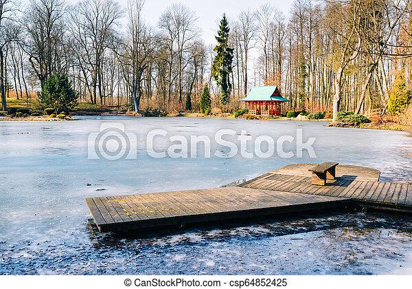 wooden jetty on a frozen lake in a garden - csp64852425