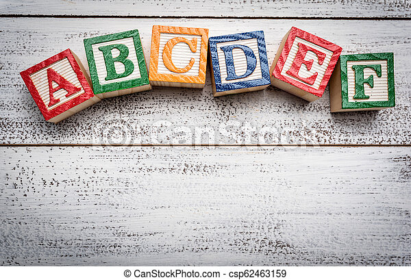 Wooden letter blocks on a white distressed wood background - csp62463159
