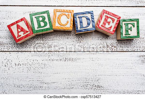 Wooden letter blocks on a white distressed wood background - csp57513427