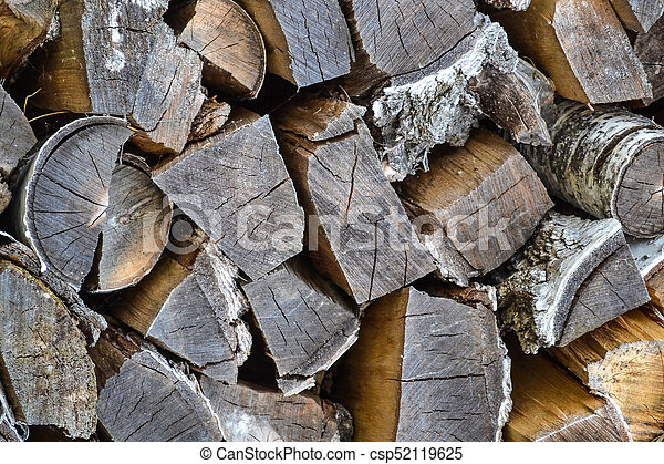 Wooden logs natural abstract background. Texture of short and long wooden logs with dark brown bark. Wood, firewood - csp52119625