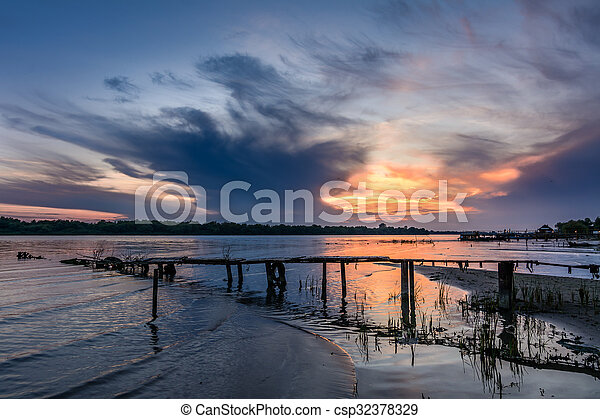 Wooden pier at sunset in the summer. Horizontal view of a wooden pier near a muddy shoreline over sunset sky on background - csp32378329