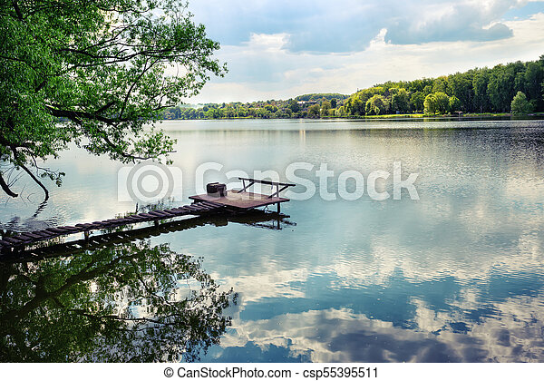 Wooden pier for fishing on the lake - csp55395511