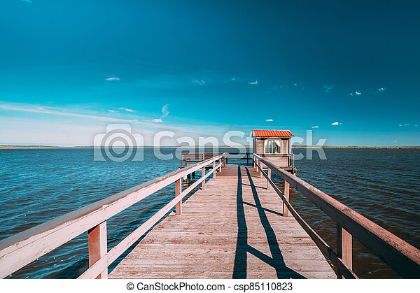 Wooden Pier For Fishing, Small House Shed And Beautiful Lake Or River In Background. Picturesque Natural Landscape In Berezinsky, Biosphere Reserve, Belarus - csp85110823