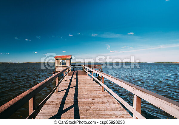 Wooden Pier For Fishing, Small House Shed And Beautiful Lake Or River In Background. Picturesque Natural Landscape In Berezinsky, Biosphere Reserve, Belarus - csp85928238