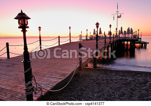 Wooden pier lighted by pink sunrise glow - csp4141377