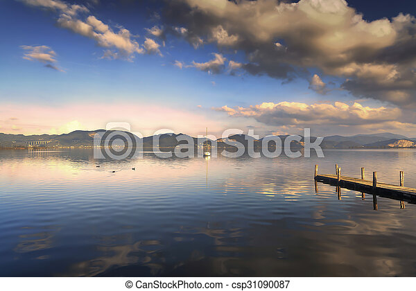 Wooden pier or jetty and on a blue lake sunset and sky reflection on water. Versilia Tuscany, Italy - csp31090087
