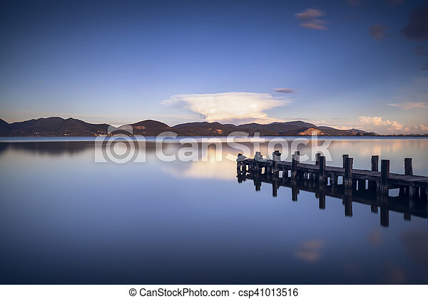 Wooden pier or jetty on a blue lake sunset and sky reflection on water. Versilia Tuscany, Italy - csp41013516