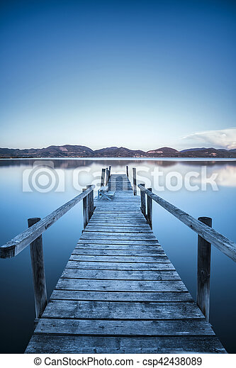 Wooden pier or jetty on a blue lake sunset and sky reflection on water. Versilia Tuscany, Italy - csp42438089
