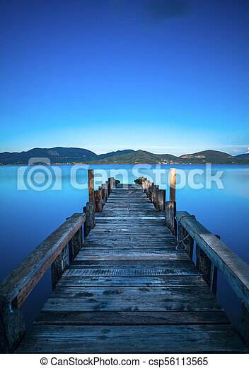 Wooden pier or jetty on a blue lake sunset and sky reflection on water. Versilia Tuscany, Italy - csp56113565