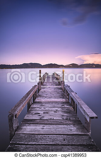 Wooden pier or jetty on a blue lake sunset and sky reflection on water. Versilia Tuscany, Italy - csp41389953
