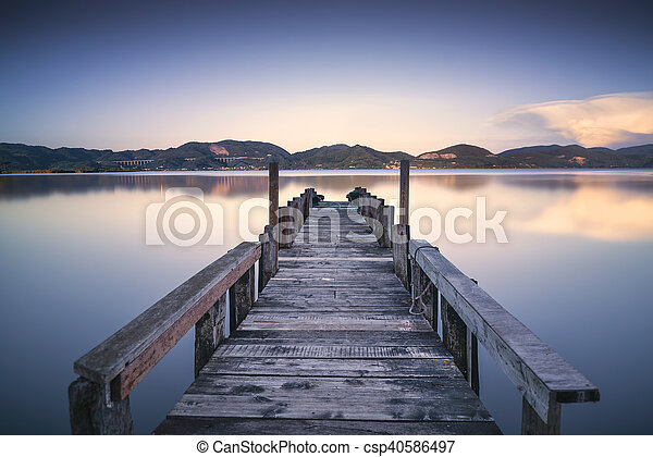 Wooden pier or jetty on a blue lake sunset and sky reflection on water. Versilia Tuscany, Italy - csp40586497